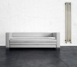 White couch in front of white concrete wall